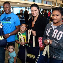 Jamaica Tourist Board's business development manager Dian Holland (left) presented gifts to the Jones family before they boarded Frontier Airlines'...