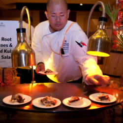 Hilton Waikoloa Village chef Dayne Tanabe serves smoked brisket with taro root potatoes at Mealani's Taste of the Hawaiian Range. // © 2013 Hilton...