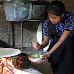 A young girl in Oaxaca cooks tortillas over the fire // © 2014 Naeyshae Ahrnberg