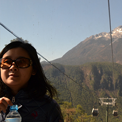 Vicky Qin, a tour director for Globus Family of Brands, on a gondola to Jade Dragon Snow Mountain's Spruce Meadow in Lijiang, China // © 2013 Mindy Poder