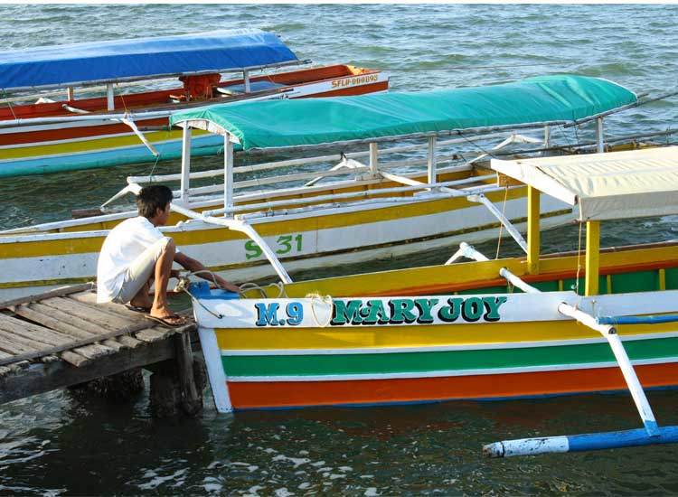 A bangka boat owner secures his boat at Lucas Wharf, the gateway to Hundred Islands. // (c) 2013 Nila Do