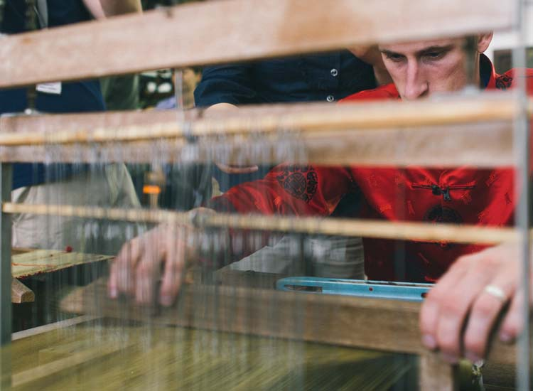 Liam Bates, recently appointed tourism ambassador for Hangzhou, tries his hand at weaving at the Dujingsheng Silk Weaving Museum. // © 2014 Hangzhou Tourism Commission