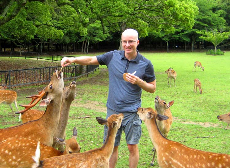 TravelAge West contributor Shane Nelson feeds a group of deer in Nara Park; visitors willing to pay $5 for rice wafers are instantly popular with the animals. // © 2014 Shane Nelson