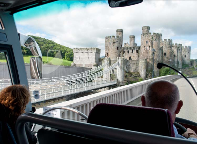 A CIE tour director/driver and local Welsh guide offer commentary on the way to Conwy Castle. // © 2014 Mindy Poder