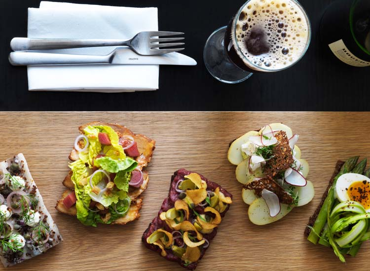 Visitors might sample Nordic cuisine at a number of renowned Copenhagen restaurants, including Aamanns Smorrebrodsdeli, where traditional smorrebrod (Danish open-faced sandwiches) get a modern twist. // © 2014 Columbus Leth