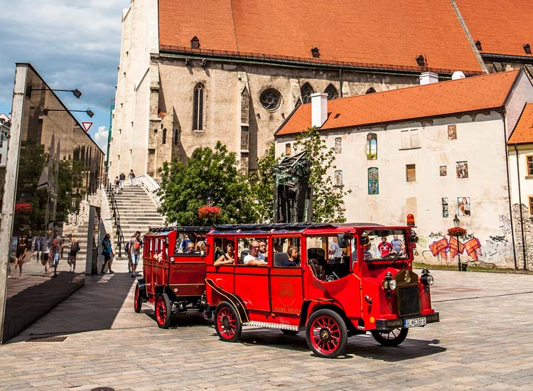 Red trams accommodate foot-weary visitors as they pass the Gothic St. Martin's Cathedral, which dates back to the early 14th century. // © 2014 Courtesy Bratislava Tourist Board