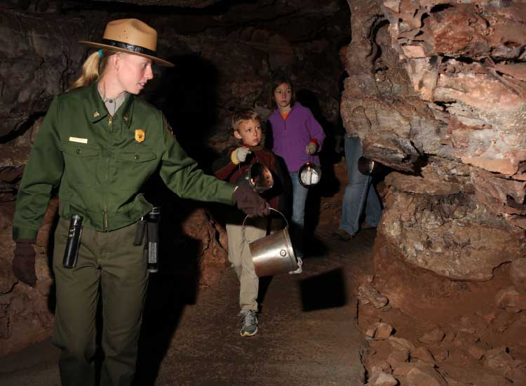 At Wind Cave National Park, visitors are guided by candlelight in a handheld bucket. // © 2014 Wind Cave National Park