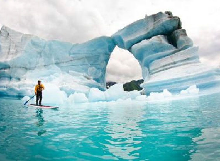 Visitors can try paddleboarding next to icebergs and glaciers at Kenai Fjords National Park. // © 2014 Liquid Adventures