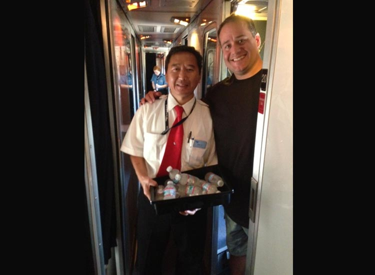 Marini inside the train with an attendant // © 2014 Amtrak Vacations